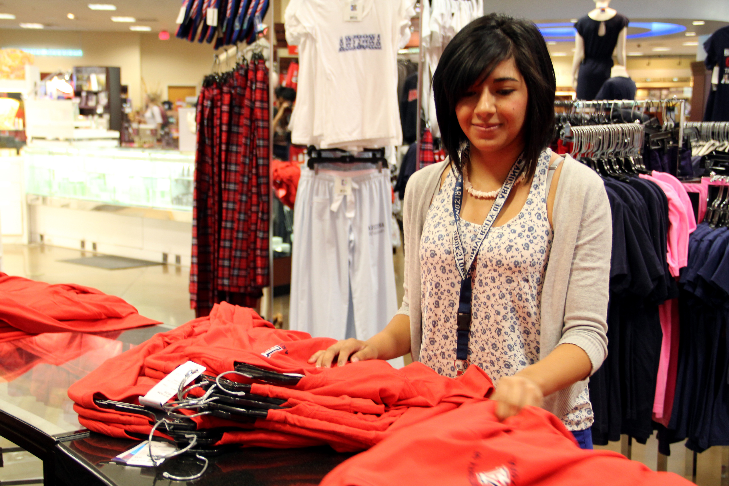 A Hispanic woman folding clothes in a store.