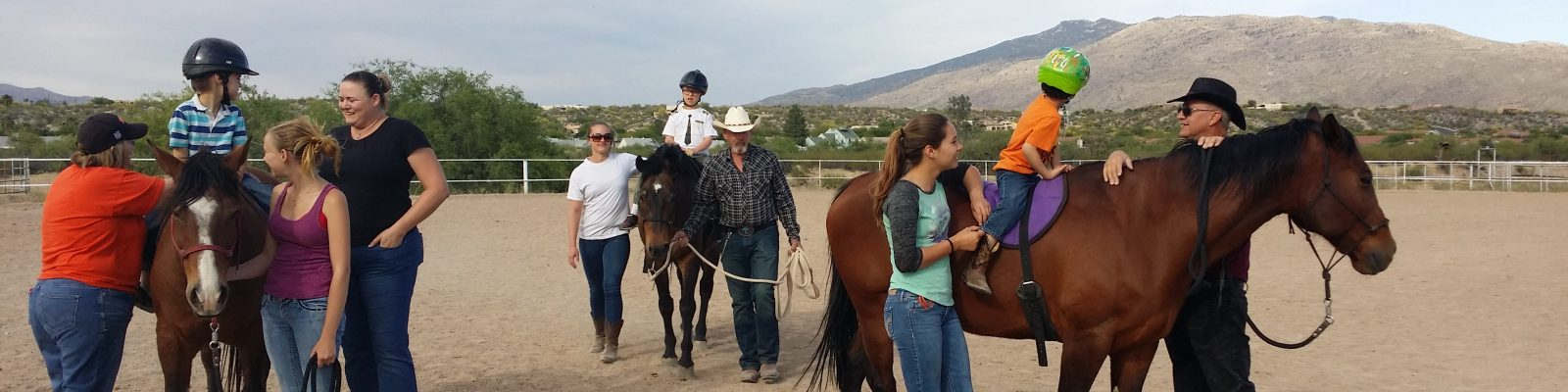 three kids riding horses with support during therapy session
