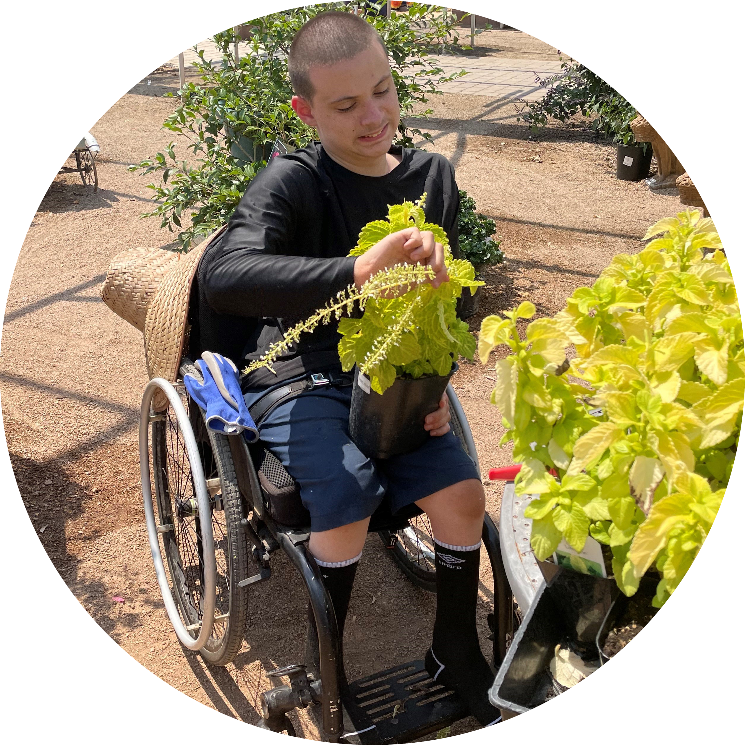 Gage - A young man with short hair in a wheelchair tending to some plants.