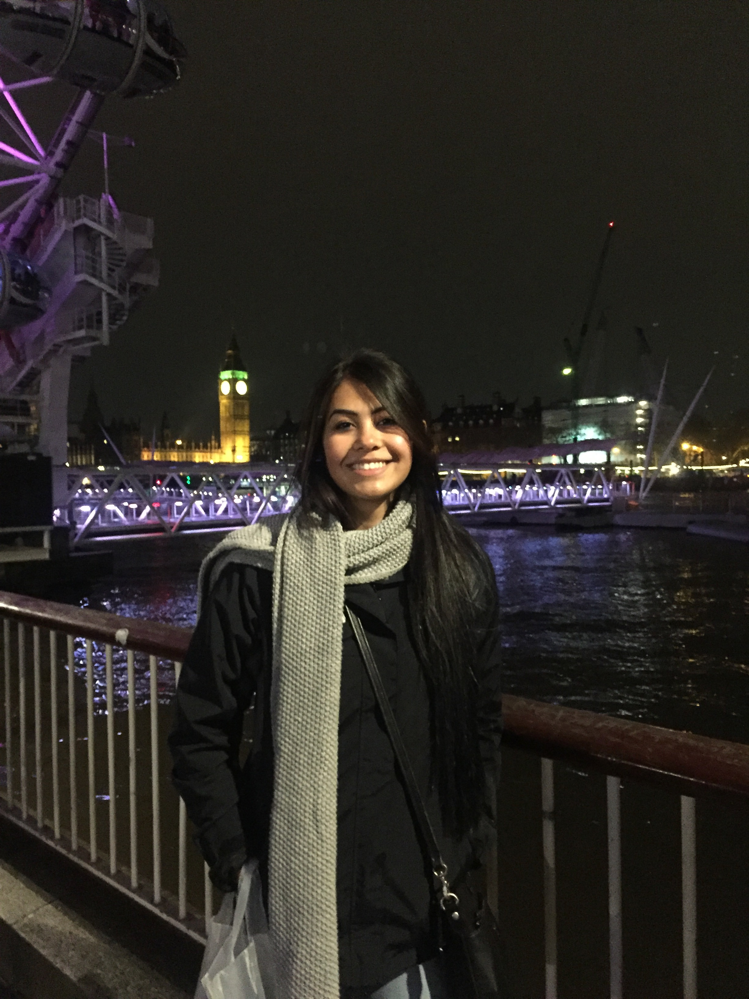 Ginger Mogel - Filipino American woman with long dark hair wearing a scarf on a bridge overlooking the river at night
