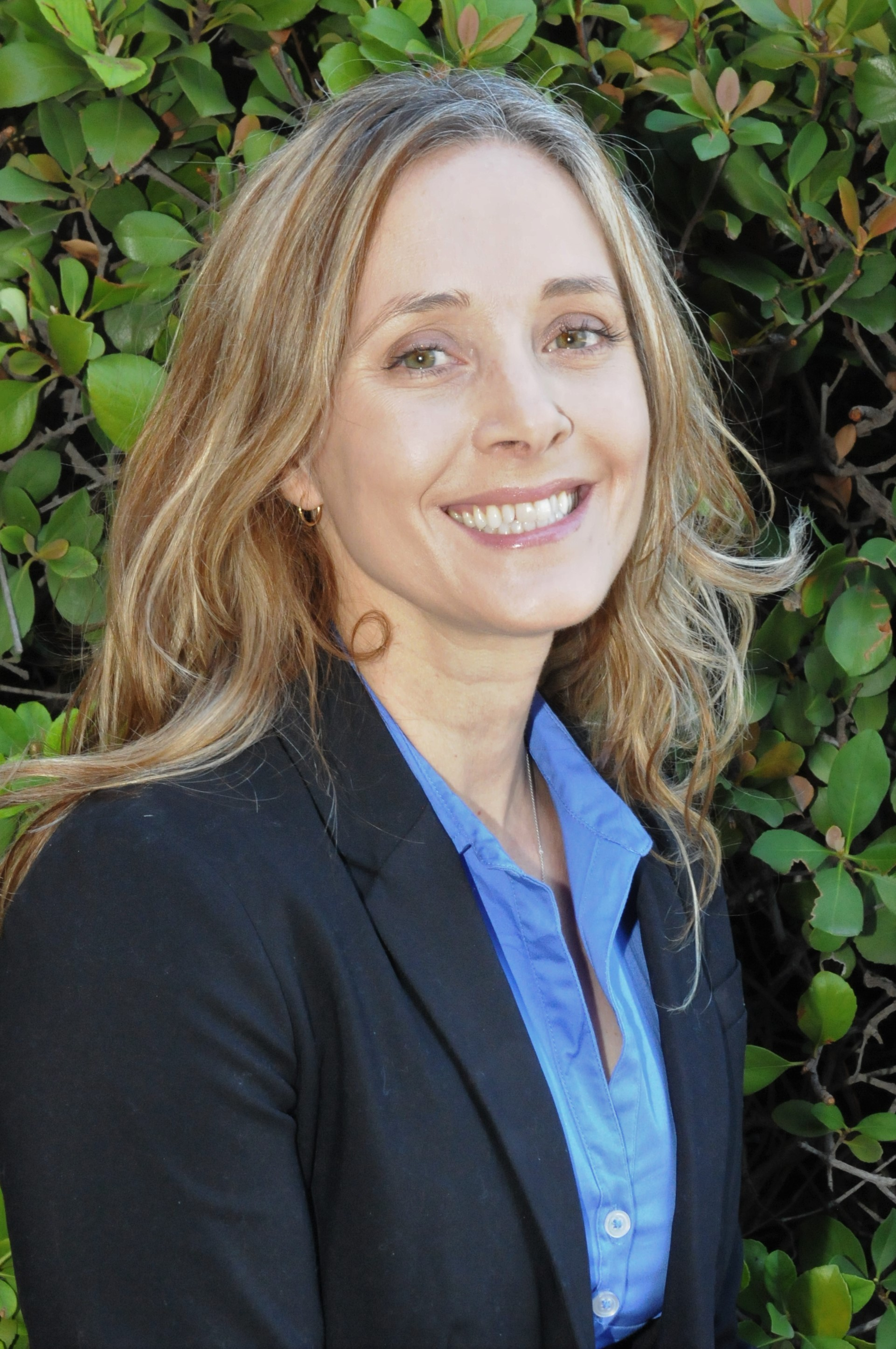 Rebecca Hartzell, headshot of honey blonde Caucasian woman in front of green foliage in a blue blazer