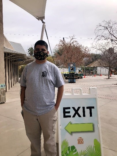 A student wearing a Reid Park Zoo t-shirt and a face mask stands near an Exit sign at the Reid Park Zoo.