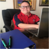 Gabe Martinez - A young adult an wearing glasses shown sitting at a desk in front of a laptop.