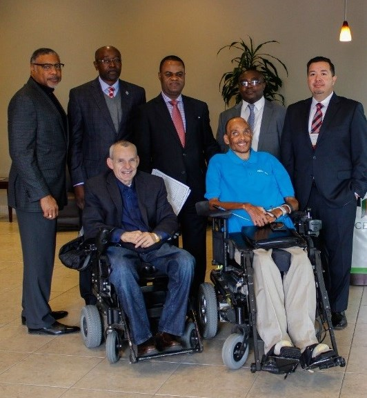 front row - two male wheelchair users; back row - five males standing