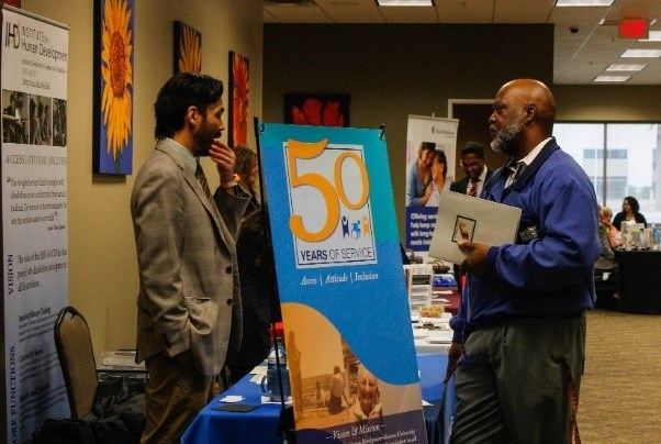 Institute for Human Development exhibitor table with attendee