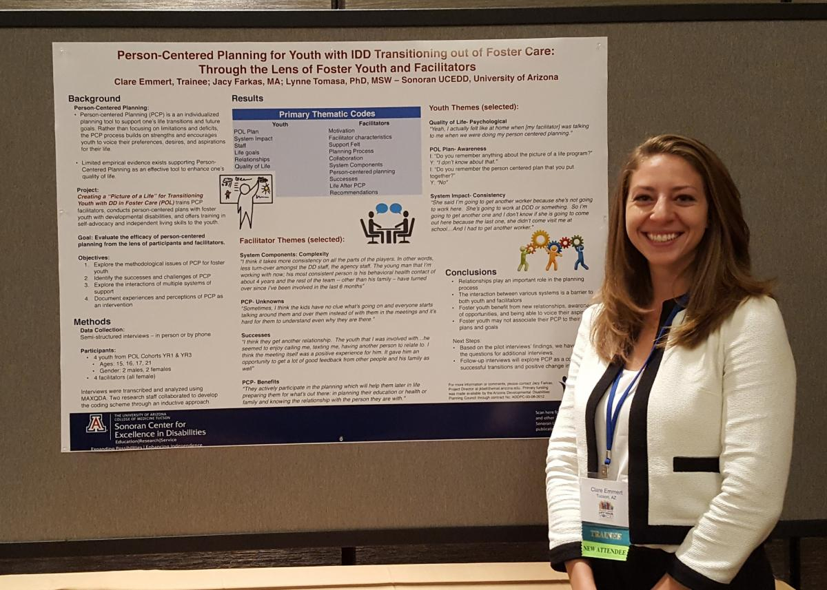 trainee, Clare standing in front of poster