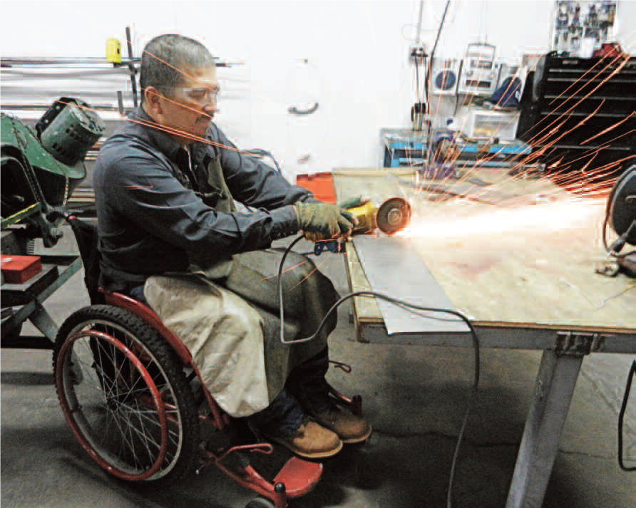 Gabriel, ARSOBO employee and wheelchair user, cutting metal for wheelchair fabrication.