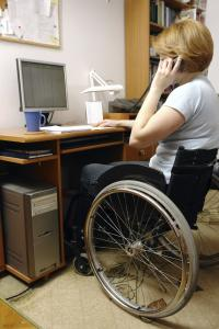 woman in a wheelchair working at her desk