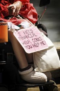 woman in a wheelchair with a sign asking for help